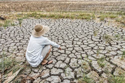 Fotografia Sad farmer is sitting in a agricultural field during the long drought