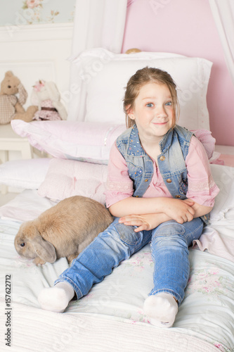 Stampa su Tela Little cute girl playing with a rabbit on the sofa at home