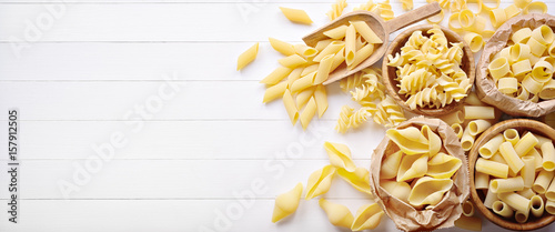 Pasta: pens, shells, rigatoni, fusilli and squid on white wooden background, top view, flat lay, copy space.