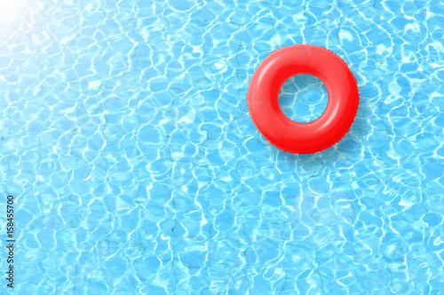 Fényképezés red swimming pool ring float in blue water and sun bright