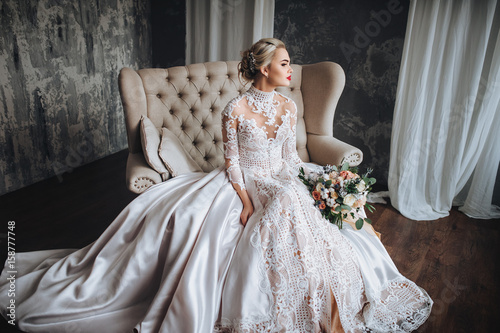 Fotografia Young beautiful bride in lace dress sits on sofa with bouquet of roses in studio