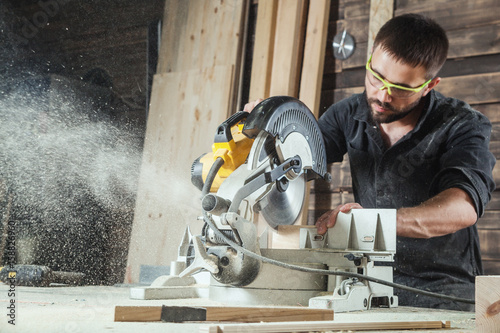 Foto Close-up as a young male construction worker carpenter saws a circular saw blade