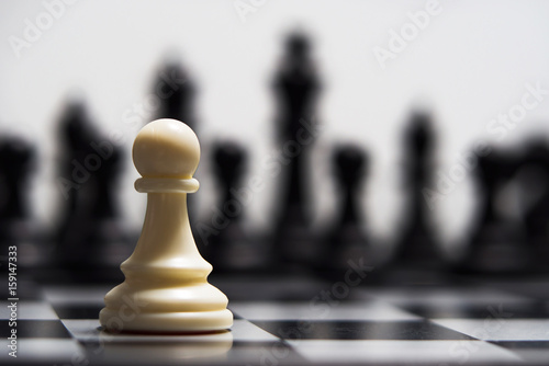 White pawn against the background of dark chess pieces Fototapet