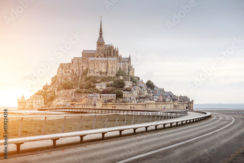 Canvas Print Sunset view on the famous Mont Saint Michel abbey with bridge during the tide in