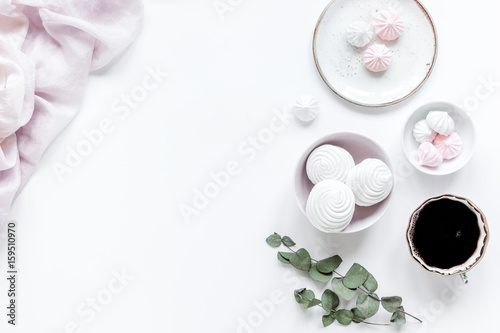 woman desk with plant, coffee and marsh-mallow in spring desing on white background flat lay mock-up