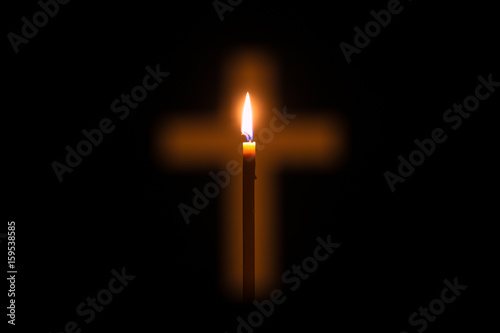Canvas Print Candle is glowing through hole in shape of Christian cross