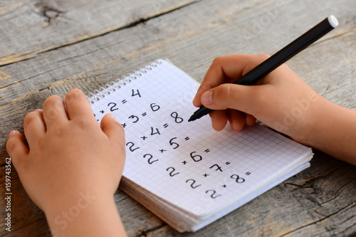 Child solves math examples. Child holds a marker in his hand and writes answers to multiplication examples in a notebook. Learning multiplication table concept