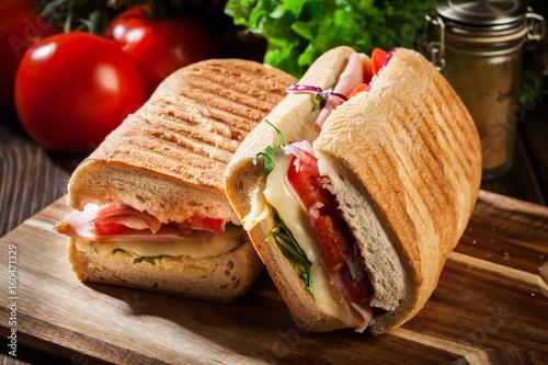 Toasted panini with ham, cheese and arugula sandwich