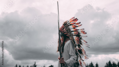 Fotografia Little girl playing outdoors in the field, wearing Indian headdress, pretending to be a native American