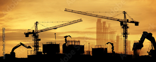 tower cranes at construction site and city background