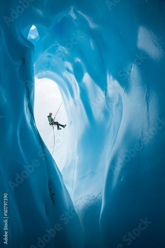 Stampa su Tela Man Rappelling past opening of blue ice cave on Matanuska Glacier, Alaska