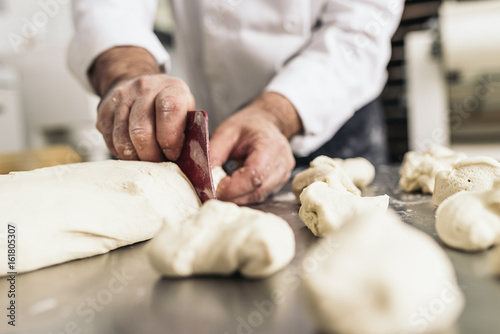 Tableau sur Toile Baker kneading dough in a bakery.