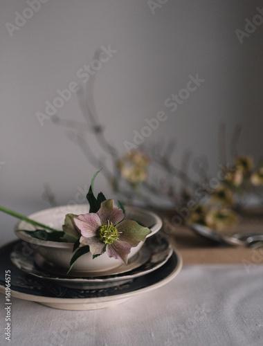 Im Restaurant wird der Tisch eingedeckt und  mit Blumen und Zweigen dekoriert