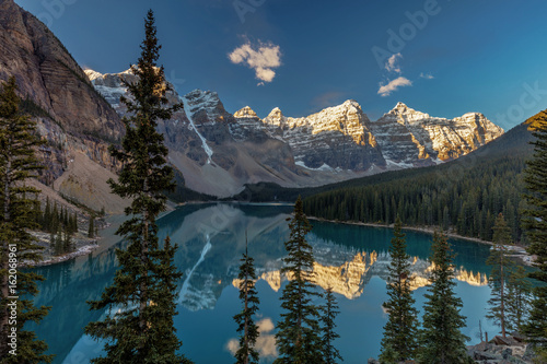 Majestic Moraine Lake in Banff National Park, Alberta. Stunning natural beauty, tall snow covered peaks, lush forest and wilderness and the jewel of the Canadian rocky mountains.