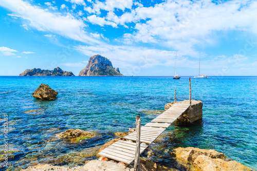 Small wooden pier in Cala d'Hort bay and view of Es Vedra island, Ibiza island, Spain
