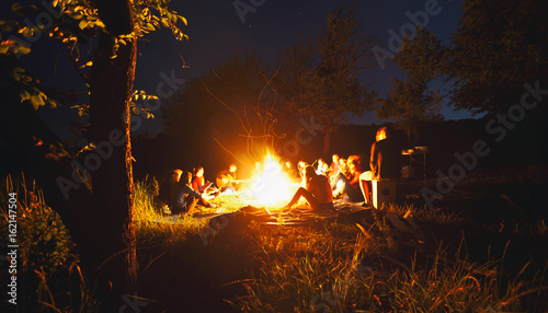 Tablou Canvas The company of young people are sitting around the bonfire and singing songs