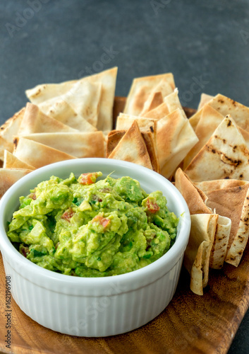 Guacamole vertical view. Guacamole is a avocado based dip, traditionally a mexican (Aztecs) dish. Healthy and easy to make at home with a few simple ingredients. Excellent as party food or at bars.