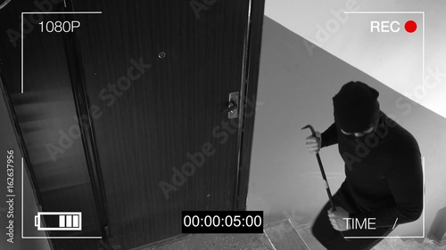 Photo See CCTV as a burglar breaking in through the door with a crowbar