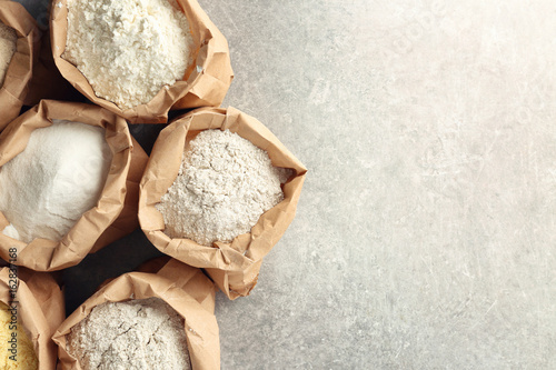 Fotografiet Paper bags with different types of flour on table
