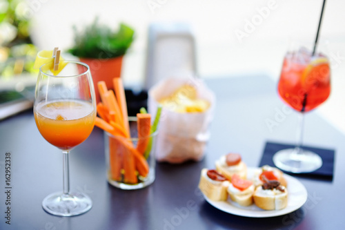Vászonkép Italian aperitives/aperitif: two glasses of cocktail and appetizer platter on th