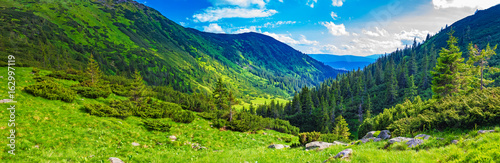 Fototapeta Majestic beautiful mountain valley on a summer day with clouds and blue sky