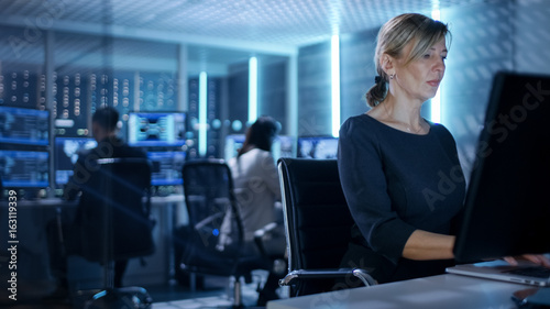 Fotografiet Female IT Engineer Works on Her Desktop Computer in Government Surveillance Agency
