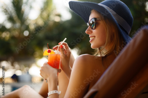 Foto Portrait of young woman with cocktail glass chilling in the tropical sun near swimming pool on a deck chair with palm trees behind