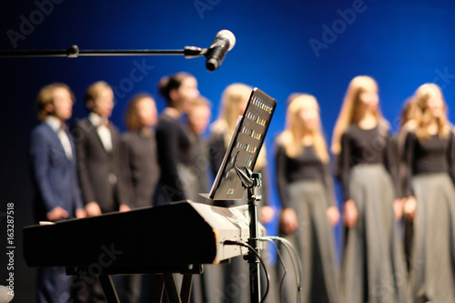 Tableau sur Toile Microphone and music stand in front of electric pianos on the stage of the theat