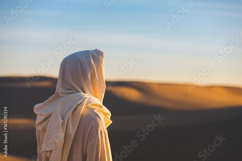 Fotografija Jesus Christ looks out at a setting sun in the sand dunes.