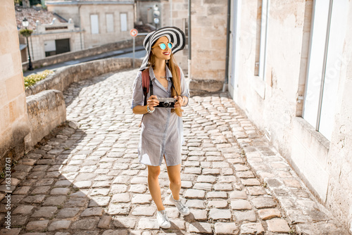 Young woman tourist walking old street at the famous Saint Emilion village in Bo Fototapet