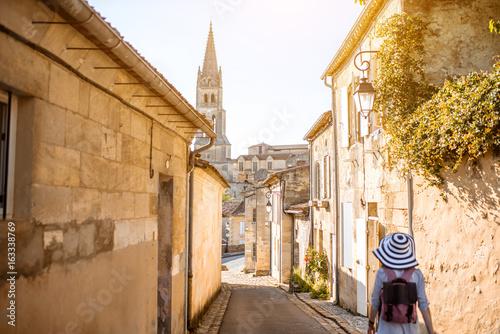 Billede på lærred Young woman tourist walking old street at the famous Saint Emilion village in Bo