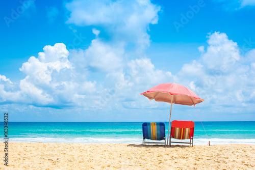 Fototapeta Beach chairs with umbrella and sand beach in summer.