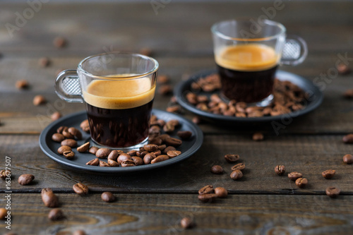 Fotografia Two cups of espresso and coffee beans on a wooden table