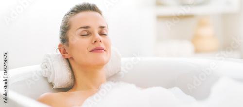 Slika na platnu Happy young woman relaxing in bathtub