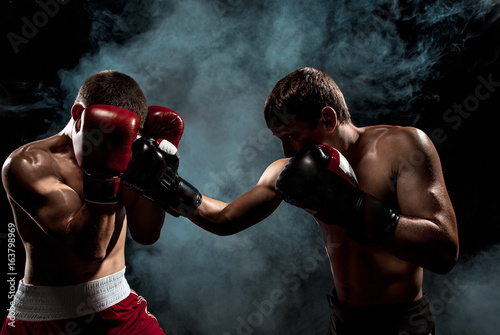 Canvas Print Two professional boxer boxing on black smoky background,
