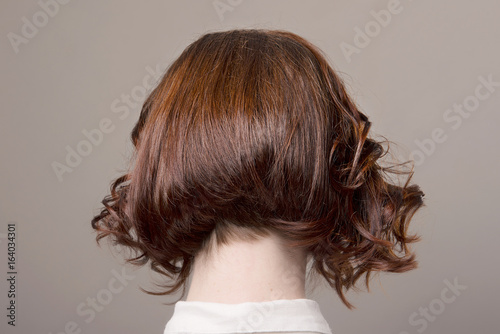 Fotografia Bob cut hairstyle with short curls in red hair on isolated grey background