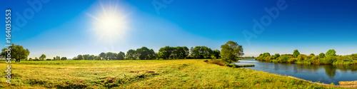 Landschaft im Sommer mit Bäumen, Wiesen, Fluss und Sonne Fototapeta