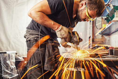 Fotografie, Tablou man weld in a processes a metal  with a  angle grinder