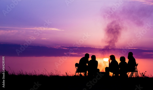 Tablou Canvas people sitting near campfire against sunset with copyspace