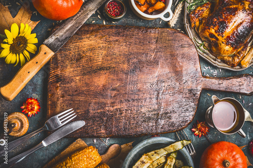 Photo Thanksgiving dinner background with  turkey ,sauce,grilled vegetables,corn ,cutlery ,  pumpkin, fall leaves and flowers arrangements around wooden gutting board, top view