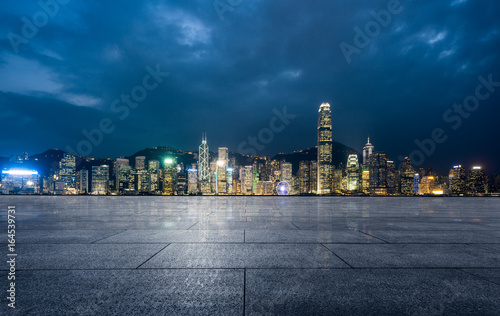 Fotografie, Obraz empty brick platform with Hong Kong skyline in background at night