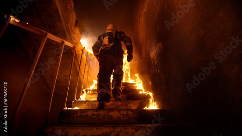 Valokuva Strong and brave Firefighter Going Up The Stairs in Burning Building
