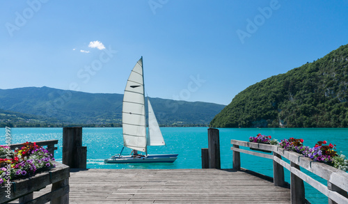 Small boat  sailing past a wooden dock on Lac d'Annecy, France.