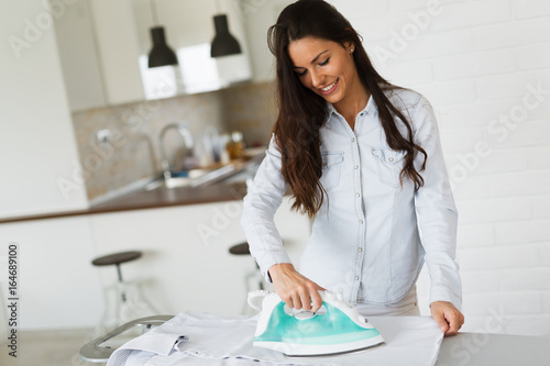 Stampa su Tela Portrait of young beautiful woman ironing clothes