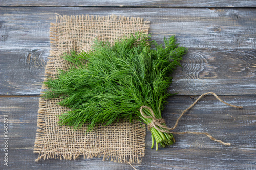 Fotografering Bunch of fresh dill on a wooden surface with free space