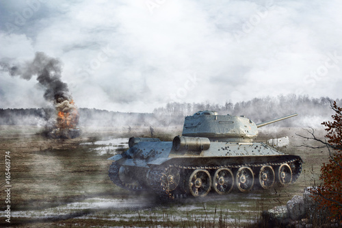 Canvas Print Soviet Tank goes through the swamp in the background of a burning tank