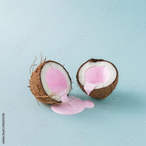 Kokos pęknięty na pół z różowym nalewaniem mleka. Minimalizm. Kreatywna koncepcja żywności.