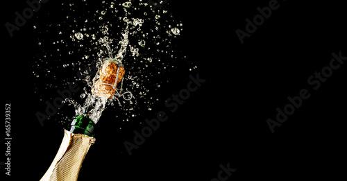 Photo Champagne cork popping and splashing on black background