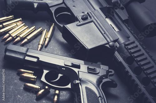 Slika na platnu Handgun with rifle and ammunition on dark background