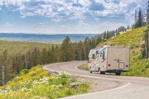 Murais de parede Camper Driving Down Road in The Beautiful Countryside Among Pine Trees and Flowers